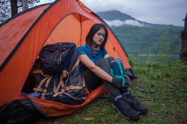 Молодая азиатская женщина, располагающаяся лагерем или пикник в лесном озере.