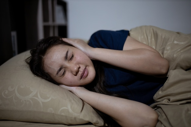 Young asian woman cannot sleep insomnia late at night. can't sleep. sleep apnea or stress. sleep disorder concept.
