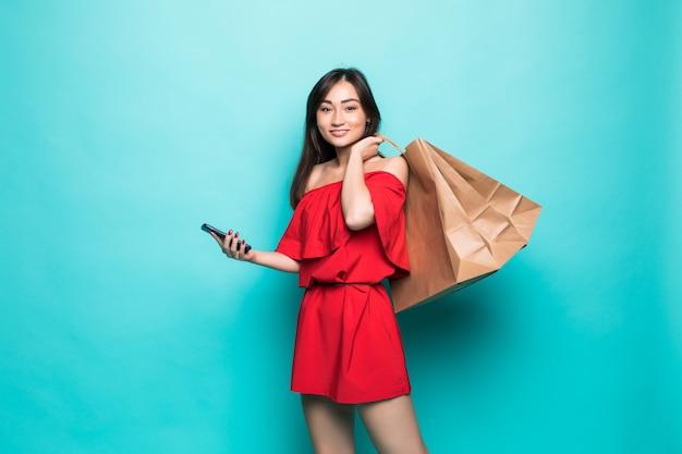 녹색 벽에 고립 된 전화로 쇼핑 가방 및 문자 메시지를 들고 젊은 아시아 여성