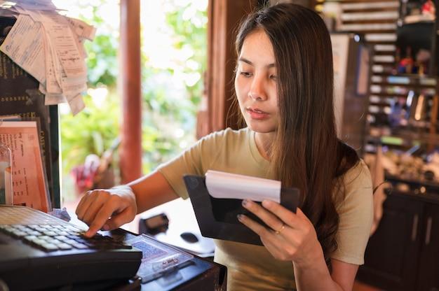 若いアジアの女性レジ係が注文の顧客をチェックし、レストランの木製カウンターでレジを押す