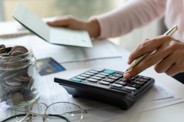 Молодая азиатская женщина проверяя счеты, налоги, баланс банковского счета и расчетные расходы по кредитной карте. концепция семейных расходов.