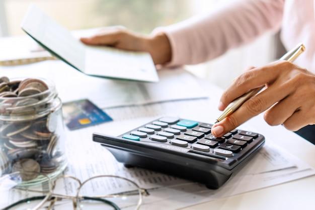 Молодая азиатская женщина проверяя счета, налоги, баланс банковского счета и расчет расходов кредитной карты. концепция семейных расходов.