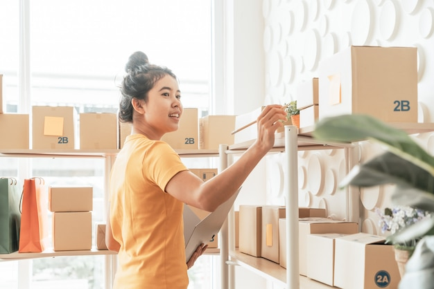 창고에서 재고 선반에 물건을 검사하는 젊은 아시아 여성