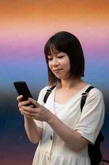 屋外で彼女の電話をチェックする若いアジアの女性