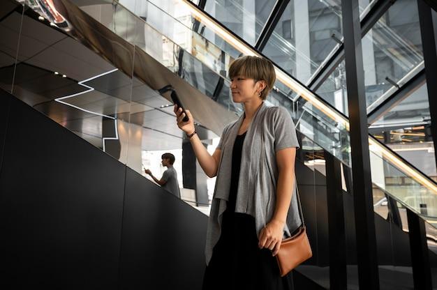 彼女の電話をチェックしている若いアジアの女性