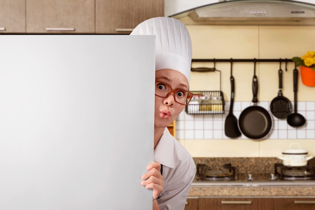 Young asian woman chef standing from behind white board