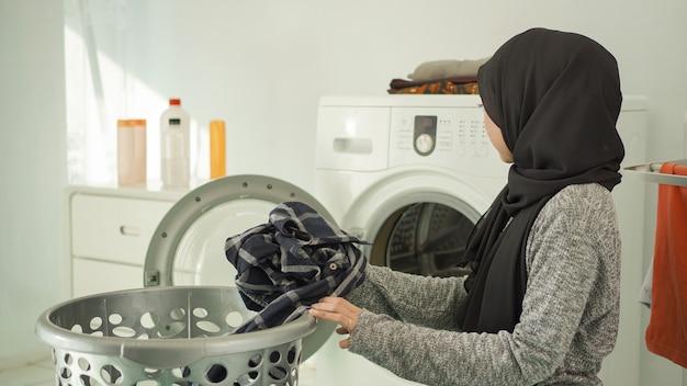 家で洗うために汚れた服を選ぶ若いアジアの女性