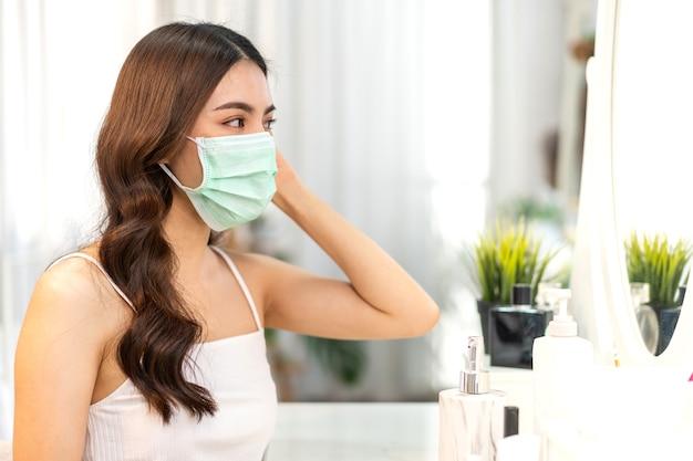 Молодая азиатская женщина чистит свежую здоровую белую кожу, глядя в зеркало в карантине от коронавируса, носит хирургическую маску для защиты лица