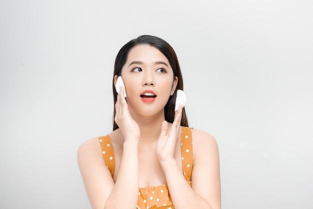 화장을 제거하기 위해 면 패드, 클렌징 로션, 페이셜 토너를 사용하여 아름다운 얼굴을 청소하는 젊은 아시아 여성.