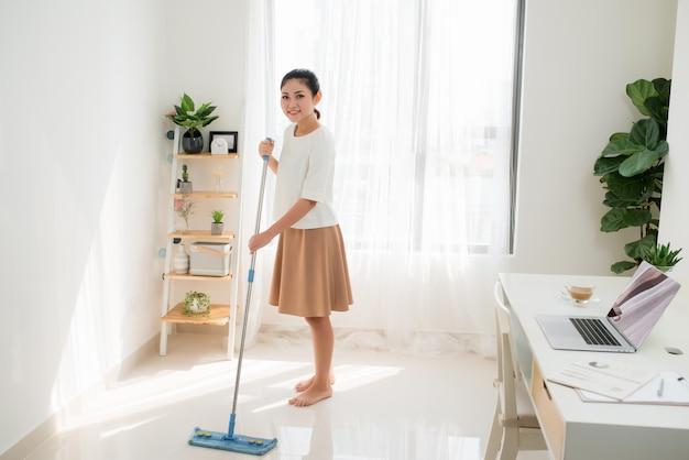 Молодая азиатская женщина чистит пол дома, делая работу по дому с привлекательной улыбкой на лице.