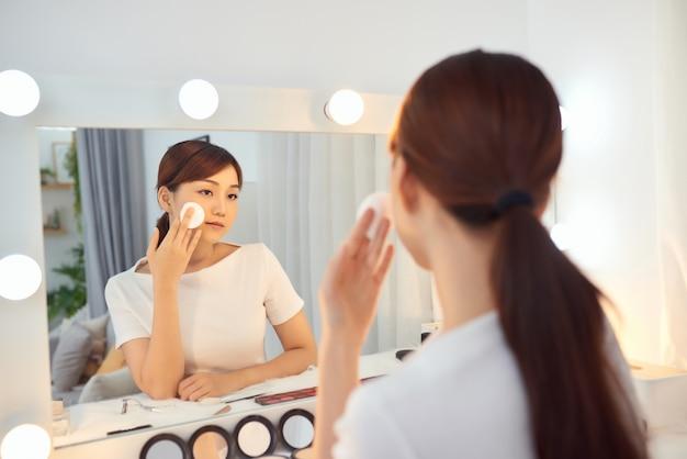 鏡の前で顔を掃除する若いアジアの女性