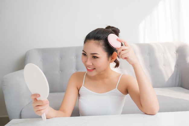 머리를 빗고 거울을 보고 있는 젊은 아시아 여성