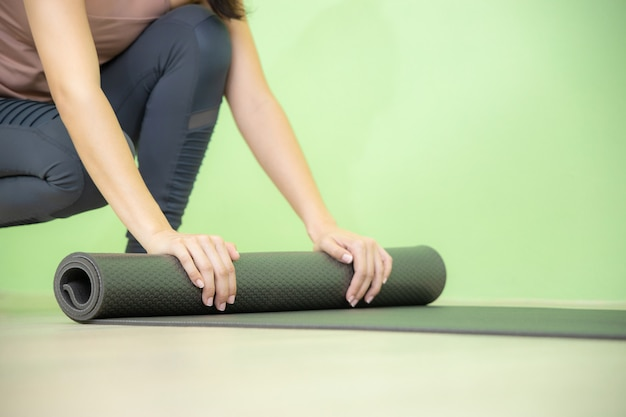 Young asian woman concentrates on rolling black yoga mat after yoga class