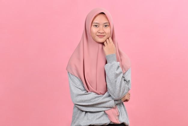 若いアジアの女性の自信は、ピンクの背景の上に分離された、カジュアルなヒジャーブを着て笑顔で始まります