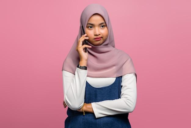 混乱し、携帯電話で話している若いアジアの女性
