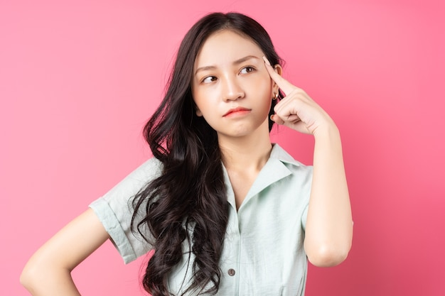 Young asian woman contemplating on pink