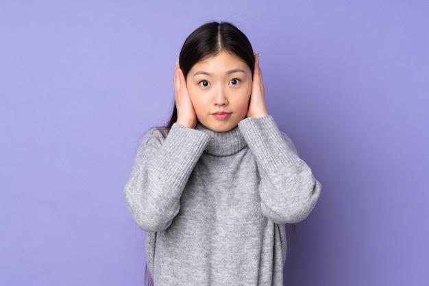 耳を覆う若いアジアの女性