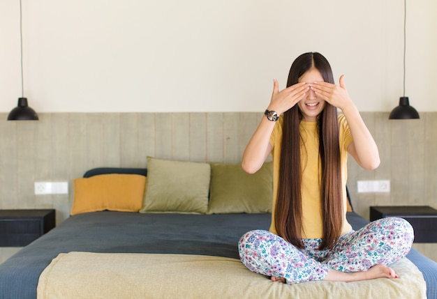 Young asian woman covering eyes with one hand feeling scared or anxious, wondering or blindly waiting for a surprise