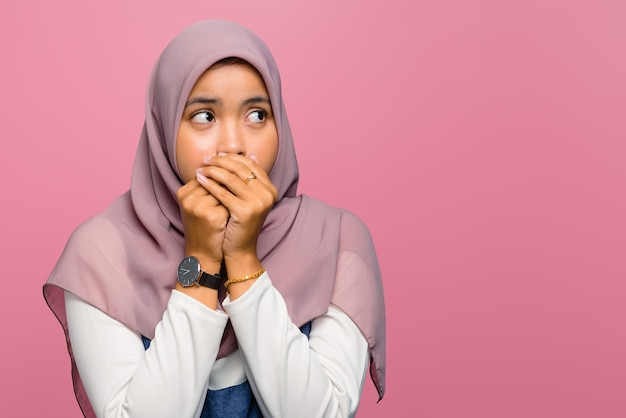 Young asian woman covering mouth and looking side
