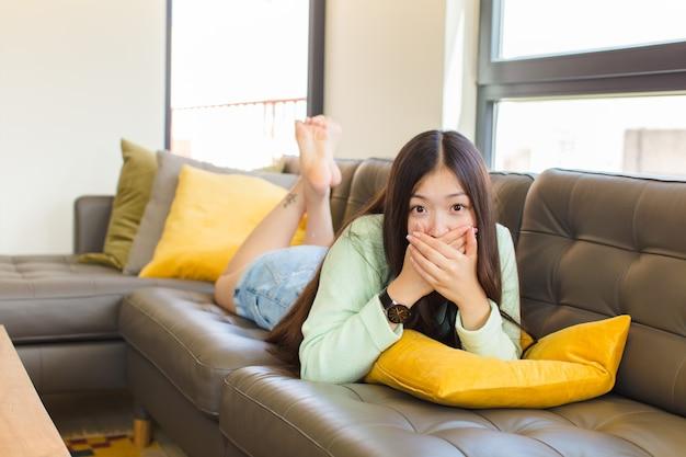 ショックを受けた、驚いた表情で手で口を覆ったり、秘密を守ったり、おっと言ったりする若いアジアの女性