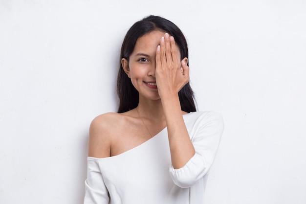 Молодая азиатская женщина, закрывающая один глаз рукой, изолированной на белом фоне