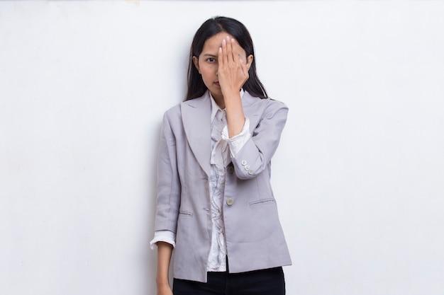 白い背景で隔離の手で片目を覆う若いアジアの女性