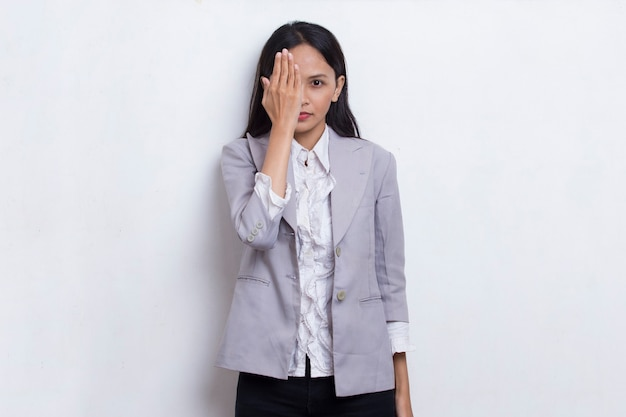 Young asian woman covering one eye with hand isolated on white background