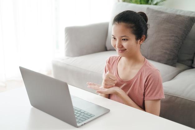 若いアジア人女性の聴覚障害者は、オンラインビデオ会議の通話学習と手話でのコミュニケーションにラップトップコンピューターを使用しています。