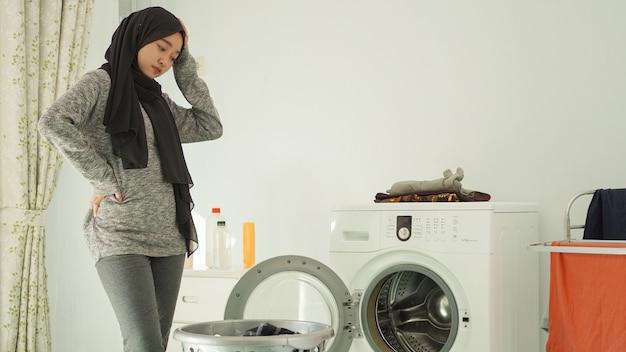 自宅で汚れた服のバスケットを見てめまいがする若いアジアの女性