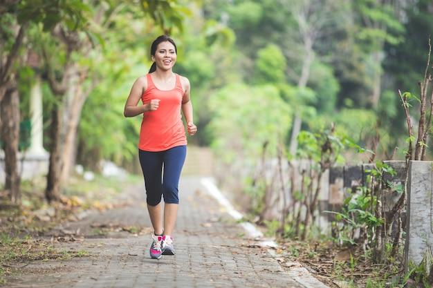 Молодая азиатская женщина делая тренировку напольную в парке, jogging