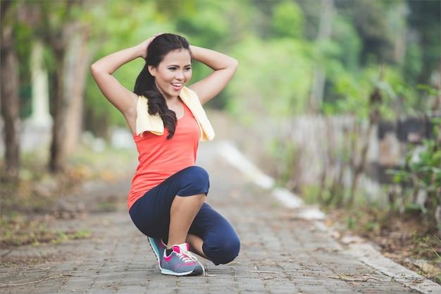 Молодая азиатская женщина делая тренировку напольную в парке, протягивая