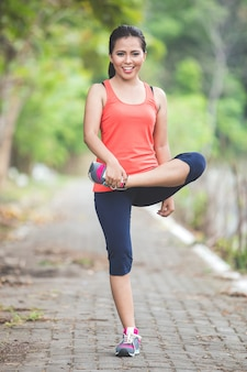 Young asian woman doing excercise outdoor in a park, stretching
