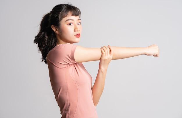Молодая азиатская женщина делает упражнения на белом