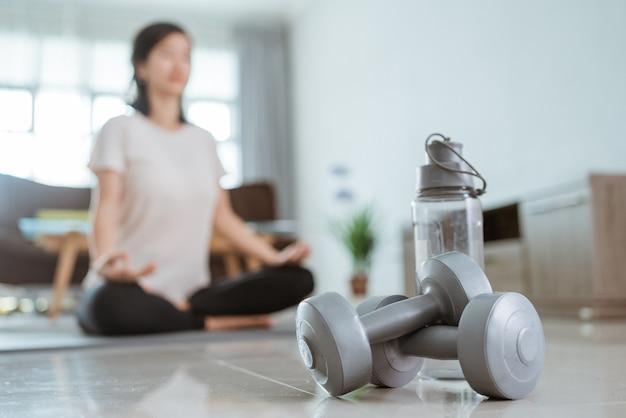 ダンベルに自分の焦点を当てて自宅で運動をしている若いアジアの女性