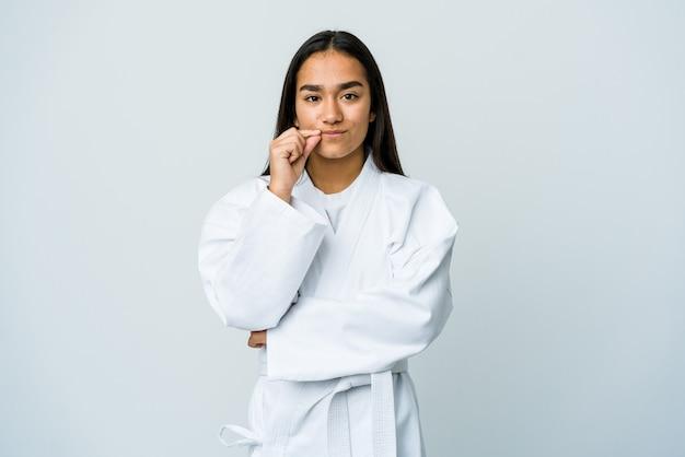 Молодая азиатская женщина занимается каратэ изолированной на белой стене с пальцами на губах, сохраняя в секрете.