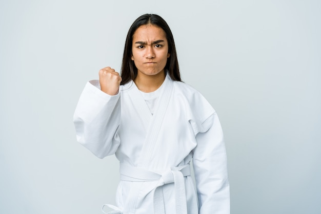 Young asian woman doing karate isolated on white wall showing fist to front, aggressive facial expression