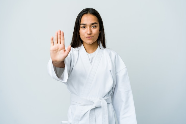 Young asian woman doing karate isolated on white wall standing with outstretched hand showing stop sign, preventing you.