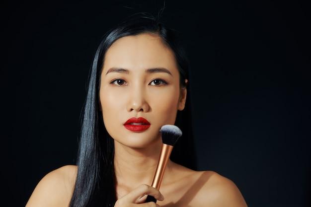 화장을 하는 젊은 아시아 여성