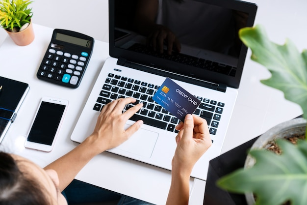 Young asian woman doing research work for her business with computer laptop while holding credit card at home, top view and copy space