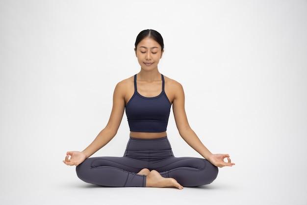 Молодая азиатская женщина делает практику йоги, изолированную на белом фоне