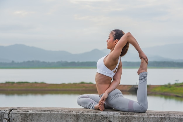 Young asian woman doing yoga on the river bank.