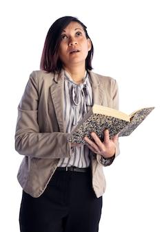 白い壁に本を着たアジアの若い女性