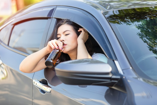 차를 운전하는 동안 맥주를 마시는 젊은 아시아 여자.