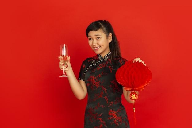Giovane donna asiatica che beve champagne e che tiene lanterna