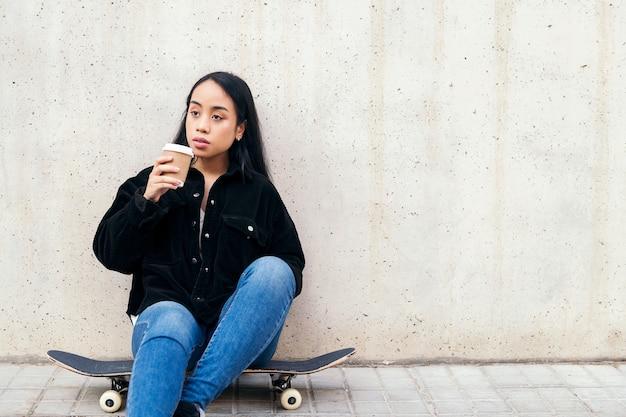콘크리트 벽에 기대어 스케이트보드에 앉아 야외에서 커피를 마시는 젊은 아시아 여성