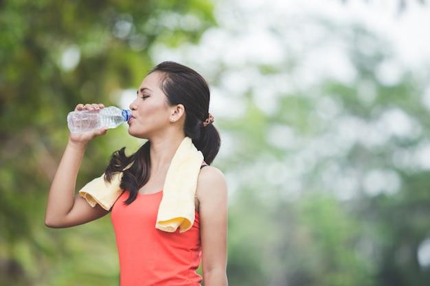 若いアジアの女性は屋外の運動をした後水を飲む