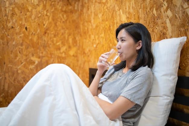 Молодая азиатская женщина пьет воду после пробуждения