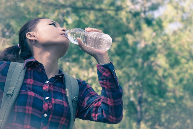 Young asian woman drinking water in the forest. hiking at summertime.