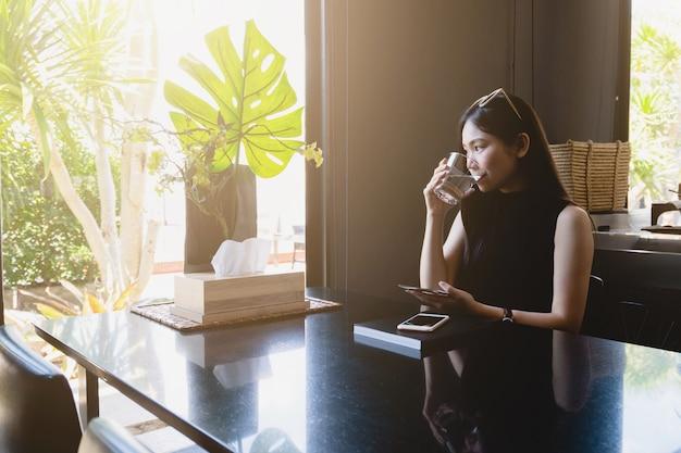 若いアジアの女性が座って家で読書しながら水を飲む