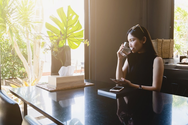 Young asian woman drinking water while sitting and reading at home